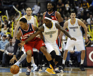 Photo - Denver Nuggets guard Ty Lawson, right, tries to steal the ball from Washington Wizards guard Bradley Beal, left, in the second half of an NBA basketball game between the Washington Wizards and the Denver Nuggets on Friday, Jan. 18, 2013, in Denver. The Wizards won 112-108. (AP Photo/Chris Schneider)