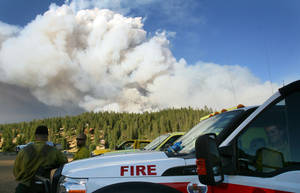 Photo -   Crews at the base stand by as smoke rises from the Shingle Fire east of Cedar City, Utah, on Monday, July 2, 2012. Evacuations were ordered as the 500-acre wildfire that broke out Sunday threatened about 100 cabins inside Dixie National Forest. In all, 10 wildfires were burning Monday across Utah. (AP Photo/The Deseret News, Scott G Winterton)