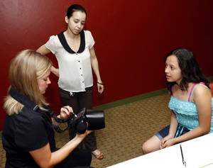 Photo -  Prevent Blindness Oklahoma vision screener Amy Romberg, left, checks the vision of Alma Benitez Contreras, 13, as Vanessa Andrade, education services coordinator for Family Expectations, watches during vision screenings by Prevent Blindness Oklahoma at Family Expectations, 3 E Main St., in Oklahoma City. Photo by Nate Billings, The Oklahoman  <strong>NATE BILLINGS -  NATE BILLINGS </strong>