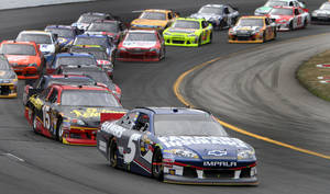 Photo -   Kasey Kahne (5) takes the lead over Clint Bowyer during a restart at the NASCAR Sprint Cup Series auto race, Sunday, July 15, 2012, at New Hampshire Motor Speedway in Loudon, N.H. Kahne won the race. (AP Photo/Jim Cole)