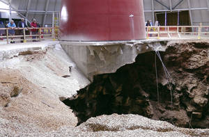 Photo - In this photo taken on Wednesday, June 11, 2014, visitors to the National Corvette Museum in Bowling Green, Ky., look down at a massive sinkhole that swallowed eight classic Corvettes. Attendance at the museum has increased since the sinkhole opened in February. (AP Photo/Dylan Lovan)