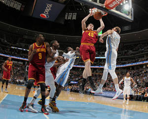 Photo - Cleveland Cavaliers center Tyler Zeller (40) dunks ball as Denver Nuggets center Timofey Mozgov, of Russia, second from right, tries to block the shot in the first quarter of an NBA basketball game in Denver, Friday, Jan. 17, 2014. Looking on are, from left, Cavaliers forward Luol Deng, of Sudan, and Nuggets forwards Quincy Miller and J.J. Hickson. (AP Photo/David Zalubowski)