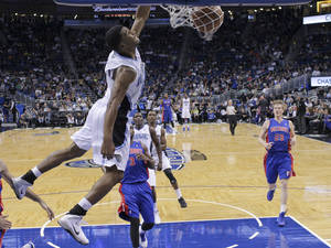 Photo - Orlando Magic's Ronnie Price, front left, dunks the ball as he gets out in front of Detroit Pistons' Rodney Stuckey (3) and Kyle Singler (25) during the first half of an NBA basketball game in Orlando, Fla., Friday, Dec. 27, 2013. (AP Photo/John Raoux)