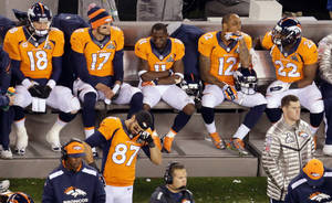 Photo - Denver Broncos' Peyton Manning sits with teammates late in the second half of the NFL Super Bowl XLVIII football game against the Seattle Seahawks, Sunday, Feb. 2, 2014, in East Rutherford, N.J. The Seattle Seahawks won 43-8. (AP Photo/Mel Evans)