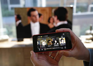 "Photo - The feature that lets the new Amazon Fire Phone send a movie or TV show wirelessly to a compatible television while the the phone serves as a ""second screen"" to display information about actors, locations, and scenes is shown, Wednesday, June 18, 2014, in Seattle. (AP Photo/Ted S. Warren)"