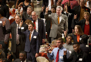 Photo - Texas head coach Mack Brown, right in gray suit, stands for the school song during the University of Texas Longhorns Honors banquet at the Frank Erwin Center in Austin on Friday Dec.13, 2013.  At left is the new Texas  Athletic Director Steve Patterson.   (AP Photo/Austin American-Statesman, Jay Janner)