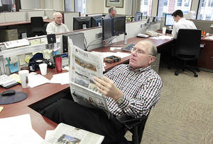Photo - Mike Gilbert, vice president of institutional sales for BOSC Inc., reads a newspaper Monday in the trading room of the firm's Oklahoma City office. Markets were closed Monday because of Hurricane Sandy, but the room remained staffed. Photos by David McDaniel/The Oklahoman