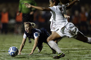 Photo - Penn State's Taylor Schram, left, falls as Florida State's Casey Short, right, clears a ball during an NCAA women's college soccer tournament semifinal, Friday, Nov. 30, 2012, in San Diego. (AP Photo/Gregory Bull)