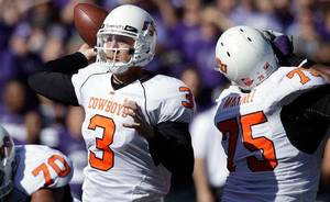 Photo - Oklahoma State quarterback Brandon Weeden (3) passes to a teammate behind the blocking of offensive linesman Nick Martinez (75) during the second half of an NCAA college football game against Kansas State, Saturday, Oct. 30, 2010, in Manhattan, Kan. Oklahoma State won 24-14. (AP Photo/Orlin Wagner)