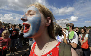 Photo -   Demonstrators with painted faces chant slogans in support of the Russian punk group Pussy Riot whose members face prison for a stunt against President Vladimir Putin, in St.Petersburg, Russia, Friday, Aug. 17, 2012. Pussy Riot members, two of whom have young children, are charged with hooliganism connected to religious hatred, but the case is widely seen as a warning that authorities will only tolerate opposition under tightly controlled conditions. (AP Photo/Dmitry Lovetsky)