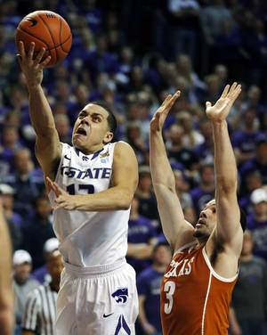 Photo - Kansas State guard Angel Rodriguez (13) gets past Texas guard Javan Felix (3) for a basket during the second half of an NCAA college basketball game in Manhattan, Kan., Wednesday, Jan. 30, 2013. Kansas State defeated Texas 83-57. (AP Photo/Orlin Wagner)