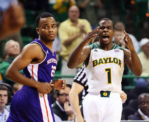 Photo - Baylor guard Kenny Chery (1), right, reacts to his 3-point play over Northwestern State guard Brison White (22) in overtime of an NCAA college basketball game, Wednesday, Dec. 18, 2013, in Waco, Texas. (AP Photo/Waco Tribune Herald, Rod Aydelotte)