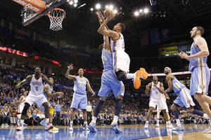 photo - Oklahoma City's Thabo Sefolosha (2) shoots the ball over Denver's JaVale McGee (34) during the NBA basketball game between the Oklahoma City Thunder and the Denver Nuggets at the Chesapeake Energy Arena on Wednesday, Jan. 16, 2013, in Oklahoma City, Okla.  Photo by Chris Landsberger, The Oklahoman