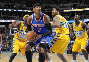 Photo - New York Knicks forward Carmelo Anthony, front, goes up to shoot as Denver Nuggets, from back left, guard Ty Lawson and forwards Wilson Chandler and J.J. Hickson cover in the first quarter of an NBA basketball game in Denver, Friday, Nov. 29, 2013. (AP Photo/David Zalubowski)