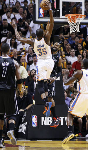 Photo - Miami Heat's Ronny Turiaf (21) tries to block Oklahoma City Thunder's Kevin Durant (35) during the first half of an NBA basketball game in Miami, Wednesday, April 4, 2012. (AP Photo/J Pat Carter) ORG XMIT: FLJC103