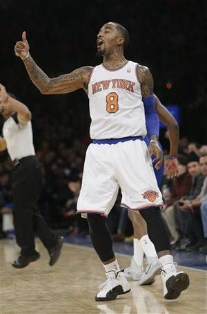Photo - New York Knicks' J.R. Smith (8) reacts after scoring during the first half of an NBA Basketball game game against the Detroit Pistons Tuesday, Jan. 7, 2014, in New York.  (AP Photo/Frank Franklin II)