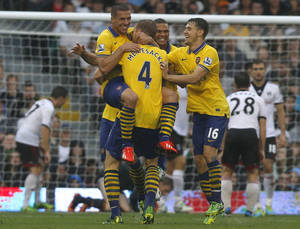 Photo - Arsenal's Lukas Podolski, left, celebrates his goal against Fulham with teammates during their English Premier League soccer match at Craven Cottage, London, Saturday, Aug. 24, 2013. (AP Photo/Sang Tan)