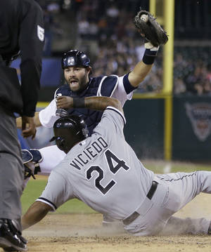 Photo - Detroit Tigers catcher Alex Avila holds up the ball to umpire CB Bucknor after tagging Chicago White Sox runner Dayan Viciedo during the seventh inning of a baseball game in Detroit, Monday, April 21, 2014. Viciedo was called safe after the umpire review. (AP Photo/Carlos Osorio)