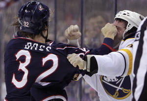 Photo - Columbus Blue Jackets' Cody Bass, left, and Buffalo Sabres' Zenon Konopka fight during the first period of an NHL hockey game, Saturday, Jan. 25, 2014, in Columbus, Ohio. (AP Photo/Jay LaPrete)