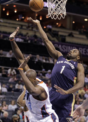 Photo - New Orleans Pelicans' Tyreke Evans (1) stretches over Charlotte Bobcats' Anthony Tolliver to score during the first half of an NBA basketball game in Charlotte, N.C., Friday, Feb. 21, 2014. (AP Photo/Bob Leverone)