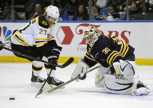 Photo - Boston Bruins' Dougie Hamilton (27) skates around Buffalo Sabres' Ryan Miller (30) during the second period of an NHL hockey game in Buffalo, N.Y., Wednesday, Oct. 23, 2013. (AP Photo/Gary Wiepert)
