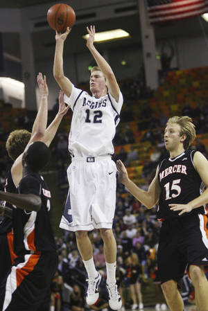 Photo - FILE - In this March 28, 2012, file photo, Utah State's Danny Berger (12) shoots against Mercer during the CollegeInsider.com college basketball tournament championship game in Logan, Utah. University spokesman Tim Vitale said that emergency responders had to use a defibrillator to get Berger breathing again after he collapsed during practice Tuesday, Dec. 4. (AP Photo/The Salt Lake Tribune, Kim Raff, File)  DESERET NEWS OUT; LOCAL TV OUT; MAGS OUT