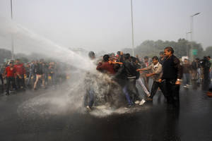 Photo - Indian police use water cannon to disperse protesters demonstrating against a gang rape and brutal beating of a 23-year-old student on a bus in New Delhi, India, Sunday, Dec. 23, 2012. The attack last Sunday has sparked days of protests across the country. (AP Photo/Tsering Topgyal)