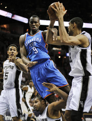 Photo - Oklahoma City Thunder's Serge Ibaka (9), of Congo, falls as he chases the ball between San Antonio Spurs' Tim Duncan, right, Boris Diaw, bottom, of France, and Cory Joseph during the second half of an NBA basketball game, Monday, March 11, 2013, in San Antonio. San Antonio won 105-93. (AP Photo/Darren Abate) ORG XMIT: TXDA107