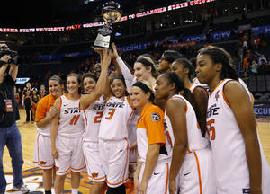 Photo - The Oklahoma State basketball team poses for a photo with the trophy after wining the All-College Classic women's basketball game between Oklahoma State University and South Florida at Chesapeake Energy Arena in Oklahoma City, Okla., Saturday, Dec. 14, 2013. Photo by Bryan Terry, The Oklahoman