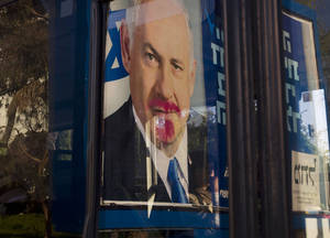 photo - A vandalized election campaign billboard of Israeli Prime Minister and Likud Party leader Benjamin Netanyahu is reflected on a bus window in Tel Aviv, Israel, Monday, Jan. 21, 2013.  The general elections will be held on Tuesday, Jan. 22, 2013. (AP Photo/Ariel Schalit)