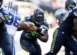 Photo -   CORRECTS TO RUNS FOR YARDAGE NOT SCORES - Seattle Seahawks' Marshawn Lynch (24) pushes aside Dallas Cowboys' Sean Lissemore as he runs for yardage in the second half of an NFL football game of Sunday, Sept. 16, 2012, in Seattle. (AP Photo/Kevin P. Casey)