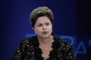 Photo - Brazil's President Dilma Rousseff speaks during a ceremony to present six new ministers to her cabinet, at the Planalto Presidential Palace, in Brasilia, Brazil, Monday, March 17, 2014.  President Rousseff announced changes in her Cabinet with an eye on the October elections in which some of her former ministers will run for Congress and regional government posts. (AP Photo/Eraldo Peres)