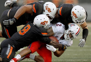 Photo - Oklahoma State's Daytawion Lowe (8), Jamie Blatnick (50), and Alex Elkins (37) bring down Arizona's Keola Antolin (2) during their game at Boone Pickens Stadium in Stillwater on Thursday night. PHOTO BY BRYAN TERRY, The Oklahoman