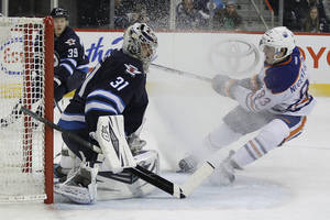Photo - Winnipeg Jets' goaltender Ondrej Pavelec (31) stops the shot from Edmonton Oilers' Ryan Nugent-Hopkins (93) as Tobias Enstrom (39) looks on during the second period of an NHL hockey game in Winnipeg, Manitoba, Saturday, Jan. 18, 2014. (AP Photo/The Canadian Press, John Woods)