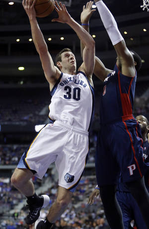Photo - Memphis Grizzlies forward Jon Leuer (30) goes to the basket against Detroit Pistons center Andre Drummond (0) during the first half of an NBA basketball game on Sunday, Jan. 5, 2014, in Auburn Hills, Mich. (AP Photo/Duane Burleson)