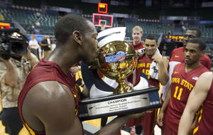 Photo - Iowa State forward Dustin Hogue gives the Diamond Head Classic championship trophy a kiss after Iowa State defeated Boise State in an NCAA college basketball game Wednesday, Dec. 25, 2013, in Honolulu. Iowa State won 70-66. (AP Photo/Eugene Tanner)