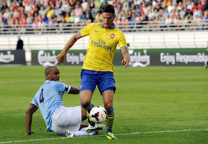Photo - Arsenal's Olivier Giroud, centre,  escapes a tackle by Manchester City's Vincent Kompany, left, during their friendly match, at the Helsinki Olympic Stadium in Helsinki, Finland on Saturday, Aug. 10, 2013.  Arsenal won 3-1. (AP Photo/Lehtikuva, Mikko Stig) FINLAND OUT