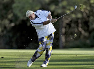 Photo - John Daly takes a divot as he hits from the seventh fairway during the second round of the Valspar Championship golf tournament at Innisbrook Friday, March 14, 2014, in Palm Harbor, Fla. (AP Photo/Chris O'Meara)