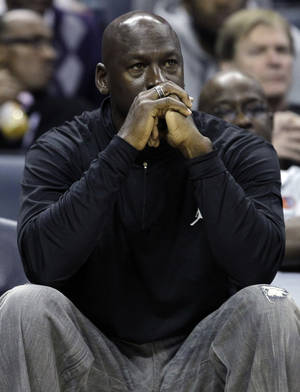 Photo -   FILE - In this Jan. 16, 2012, file photo, Charlotte Bobcats owner Michael Jordan watches during the first half of an NBA basketball game between the Bobcats and the Cleveland Cavaliers in Charlotte, N.C. Jordan's No. 23 has long been synonymous with greatness. By Thursday night, that number could have a completely different meaning. If Jordan's Charlotte Bobcats lose to the New York Knicks, it will be their 23rd consecutive loss and they'll finish the season with the worst winning percentage in NBA history. (AP Photo/Chuck Burton, File)