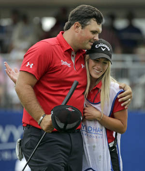 Photo - Patrick Reed, left, embraces his wife and caddie, Justine Reed, right, after making a birdie putt on the ninth hole during the second round of the Wyndham Championship golf tournament at Sedgefield Country Club in Greensboro, N.C., Friday, Aug. 16, 2013. (AP Photo/Chuck Burton)