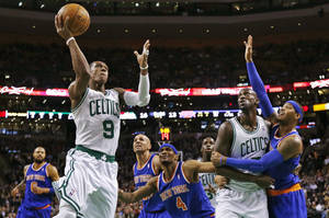 Photo - Boston Celtics guard Rajon Rondo (9) drives to the basket as Kevin Garnett blocks out New York Knicks forward Carmelo Anthony, right, during the first quarter of an NBA basketball game in Boston, Thursday, Jan. 24, 2013. (AP Photo/Charles Krupa)