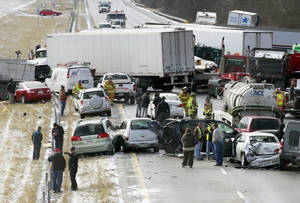 Photo - Semi-trucks and other vehicles involved in a mulit-car crash are strewn across westbound Interstate 275 between Colerain Avenue and Hamilton Avenue Monday, Jan. 21, 2013 in Cincinnati. The accident left about 20 people injured. There have been three separate highway pileups involving dozens of vehicles in Ohio. Authorities say as many as 50 vehicles could be involved in a pileup on Interstate 75 in southwest Ohio.  (AP Photo/Cincinatti Enquirer, Cara Owsley) NO SALES