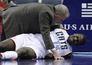 photo - A trainer checks on injured Charlotte Bobcats' Michael Kidd-Gilchrist (14) during the first half of an NBA basketball game against the San Antonio Spurs in Charlotte, N.C., Saturday, Dec. 8, 2012. (AP Photo/Chuck Burton)