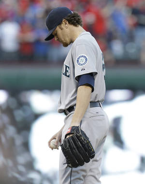 Photo - Seattle Mariners starting pitcher Blake Beavan looks down after he game up a solo home run to Texas Rangers Prince Fielder during the second inning of the MLB American League baseball game Tuesday, April 15, 2014, in Arlington, Texas. (AP Photo/LM Otero)