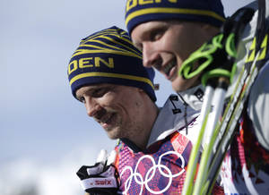Photo - Silver medalist Sweden's Johan Olsson, left, and Sweden's Daniel Richardsson, who took the bronze, pose following the flowers ceremony for the men's 15K classical-style cross-country race at the 2014 Winter Olympics, Friday, Feb. 14, 2014, in Krasnaya Polyana, Russia. (AP Photo/Gregorio Borgia)