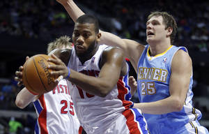 Photo - Detroit Pistons center Greg Monroe, front left, grabs a rebound in front of Denver Nuggets center Timofey Mozgov (25) during the first half of an NBA basketball game on Saturday, Feb. 8, 2014, in Auburn Hills, Mich. (AP Photo/Duane Burleson)