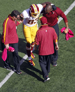 Photo -   Washington Redskins tight end Fred Davis (83) is helped off the field during the first half of an NFL football game against the New York Giants Sunday, Oct. 21, 2012 in East Rutherford, N.J. (AP Photo/Julio Cortez)