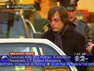 Photo - In this frame grab provided by WCBS in New York, Ryan Lanza, the 24-year-old brother of Sandy Hook Elementary School shooter Adam Lanza, is escorted by police into a cruiser in Hoboken, N.J., Friday, Dec. 14, 2012. Adam Lanza, 20, killed his mother at home and then opened fire Friday inside the elementary school where she taught, massacring 26 people, including 20 children, as youngsters cowered in fear to the sound of gunshots echoing through the building and screams coming over the intercom. (AP Photo/WCBS-TV) MANDATORY CREDIT: WCBS-TV