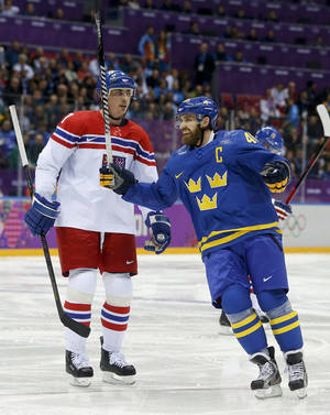 Photo - Sweden forward Henrik Zetterberg, right, reacts in front of Czech Republic defenseman Tomas Kaberle after Sweden scored a goal in the second period of a men's ice hockey game at the 2014 Winter Olympics, Wednesday, Feb. 12, 2014, in Sochi, Russia. (AP Photo/Mark Humphrey)