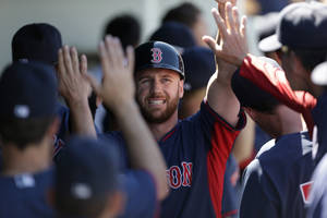 Photo - Boston Red Sox Corey Brown is greeted in the dugout after scoring on a two-run RBI double by Dustin Pedroia in the fifth inning of an exhibition baseball game against the Minnesota Twins in Fort Myers, Fla., Thursday, March 13, 2014. The Red Sox won 4-3. (AP Photo/Gerald Herbert)